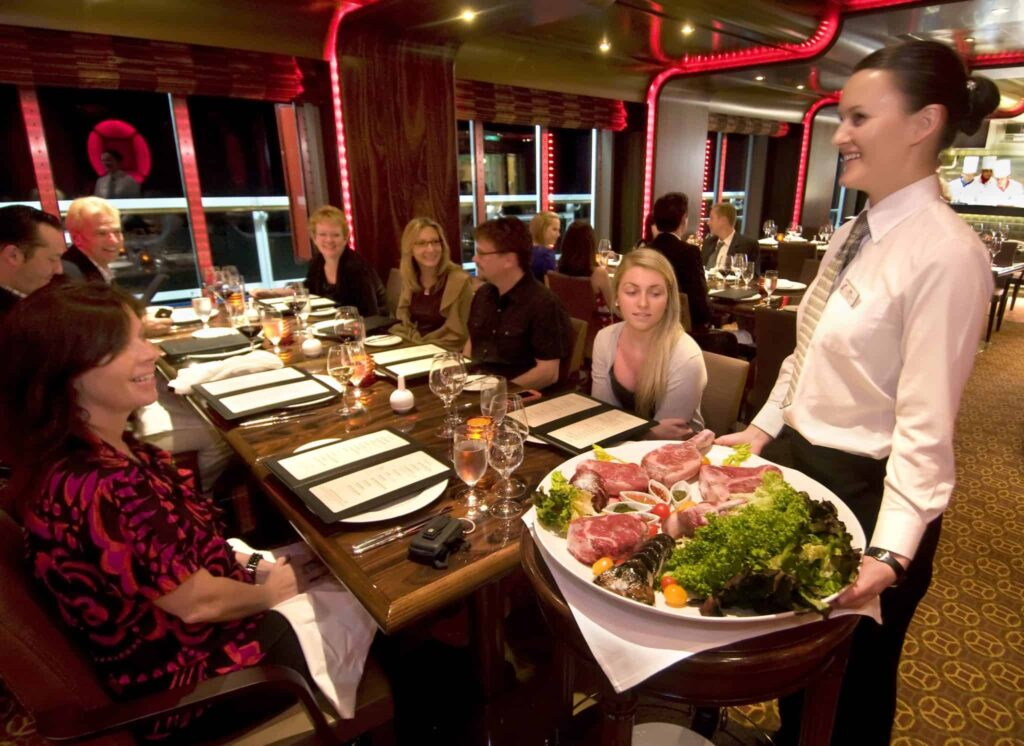 A waitress aboard the Carnival Magic presents gastronomical offerings in the ship's Prime Steakhouse Photo by Andy Newman/Carnival Cruise Lines
