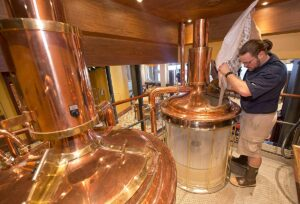 Carnival Vista Brewmaster Colin Presby pours malt into a mash tun located in the RedFrog Pub's brewery house onboard the Carnival Vista. The largest and most innovative cruise vessel in Carnival Cruise Line's fleet, Carnival Vista measures 133,500 tons, 1,055 feet long and has a guest capacity of almost 4,000 passengers. Photo by Andy Newman/Carnival Cruise Line